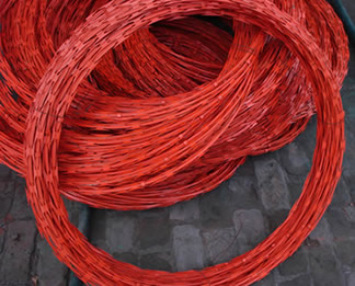Many coils PVC coated orange color concertina wire are placed together.